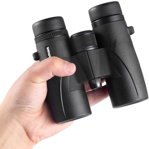 man holding compact binocular