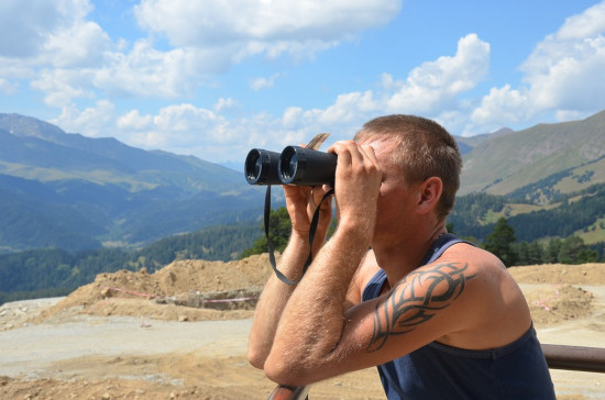 man using binocular on mountain