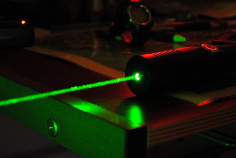 Green laser beam dark background