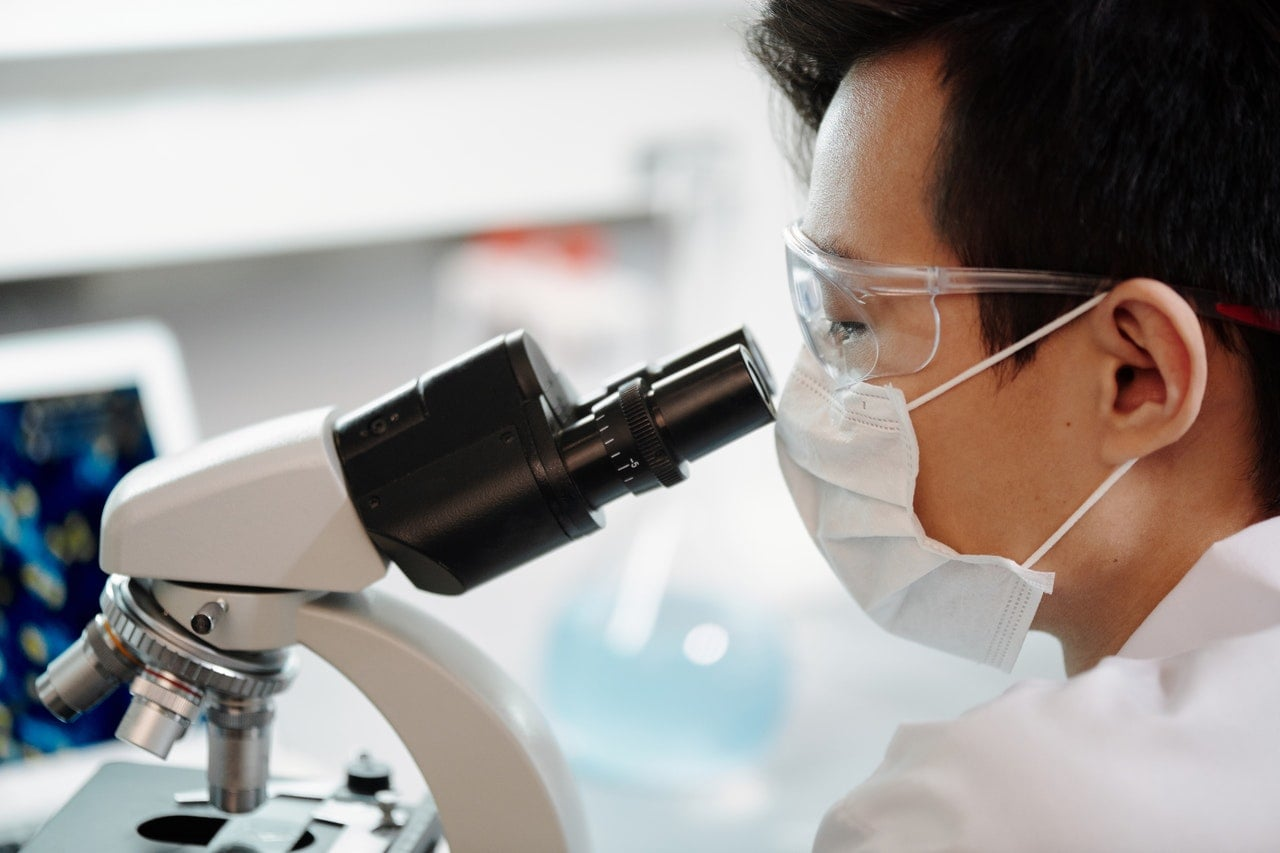 man-looking-through-a-microscope