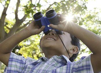 A kid using a pair of binoculars