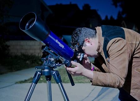 A blue refractor telescope