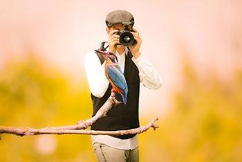 man taking photo of a hummingbird