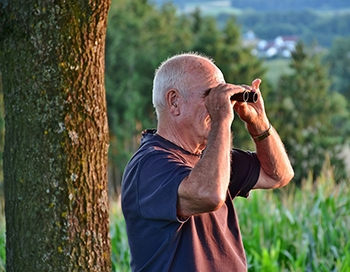 senior man holding a binocular