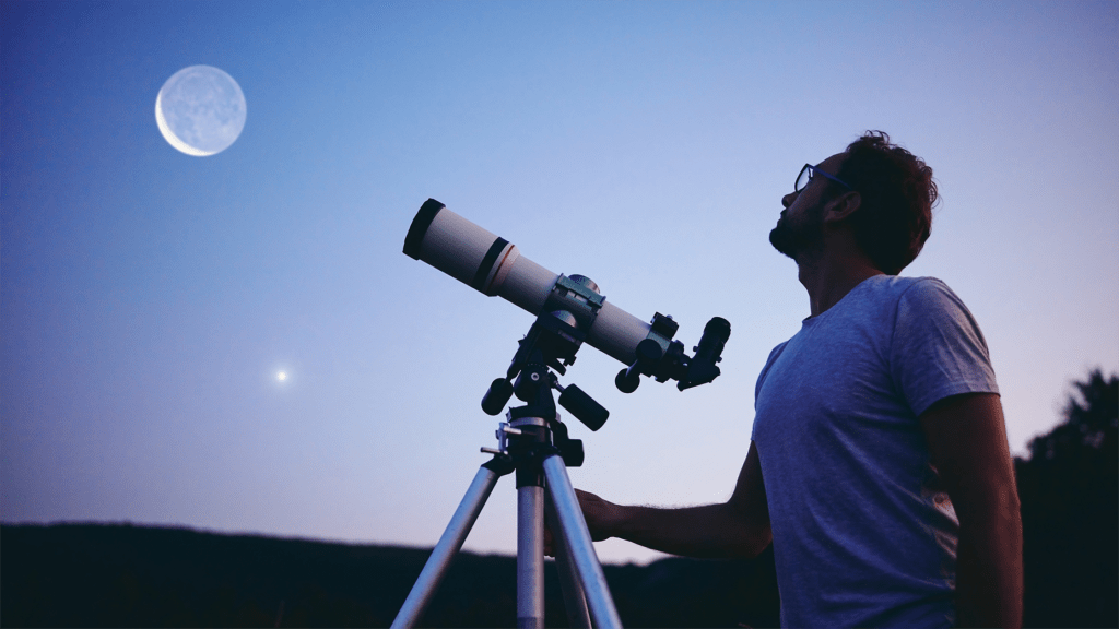 man looking at the moon in evening with telescope