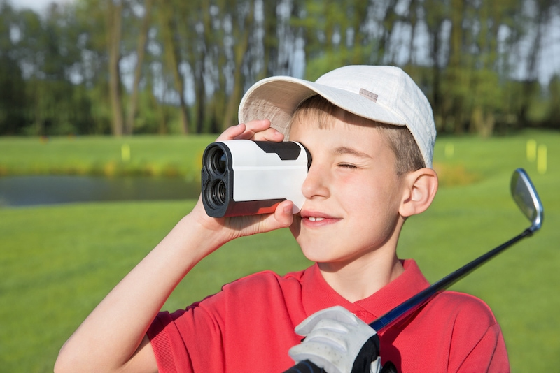 Boy golfer using rangefinder