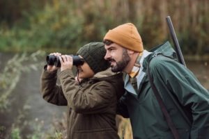 Father and son hunting with binoculars