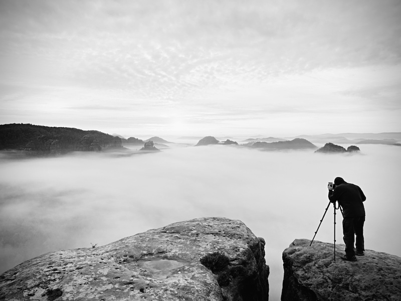 Man using rangefinder over mountain panorama