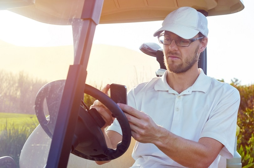 golf man relaxing on buggy cart_Daxiao Productions_shutterstock
