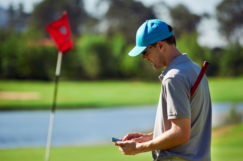 golf man with smart phone gps device_Daxiao Productions_shutterstock