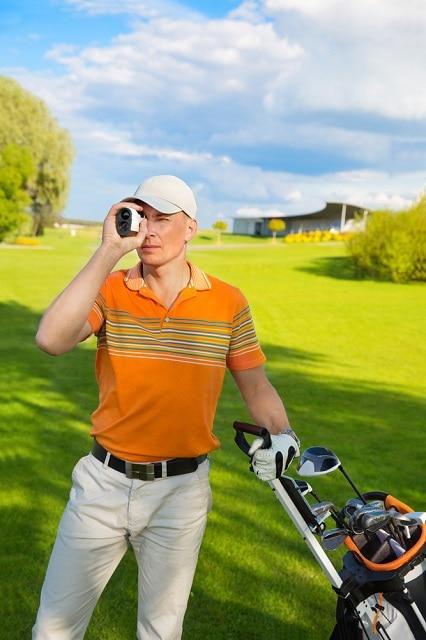 golfer watching into rangefinder_Olimpik_shutterstock