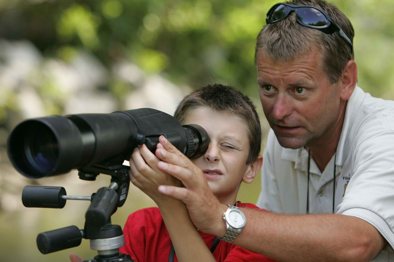 man teaching a child to use a spotting scope