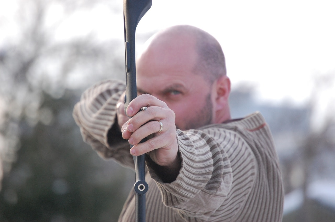 man aiming with a bow