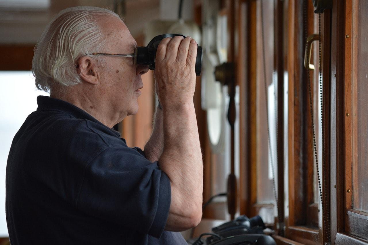 man using binoculars with glasses