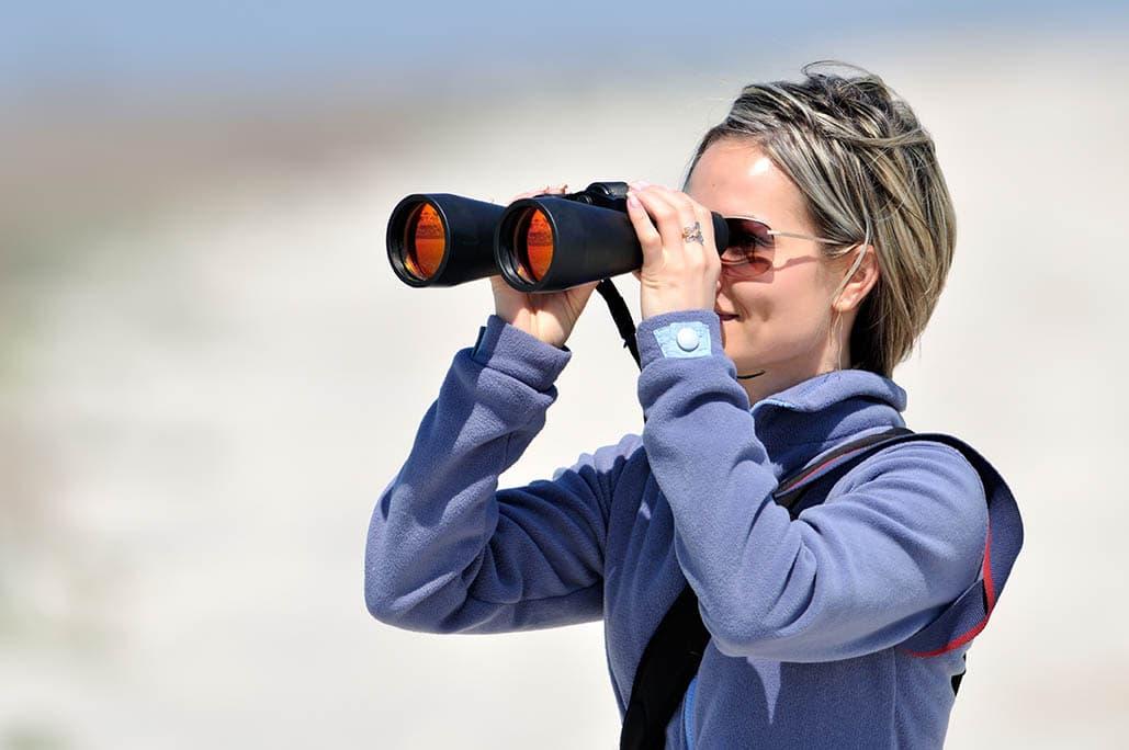 woman using binoculars with glasses