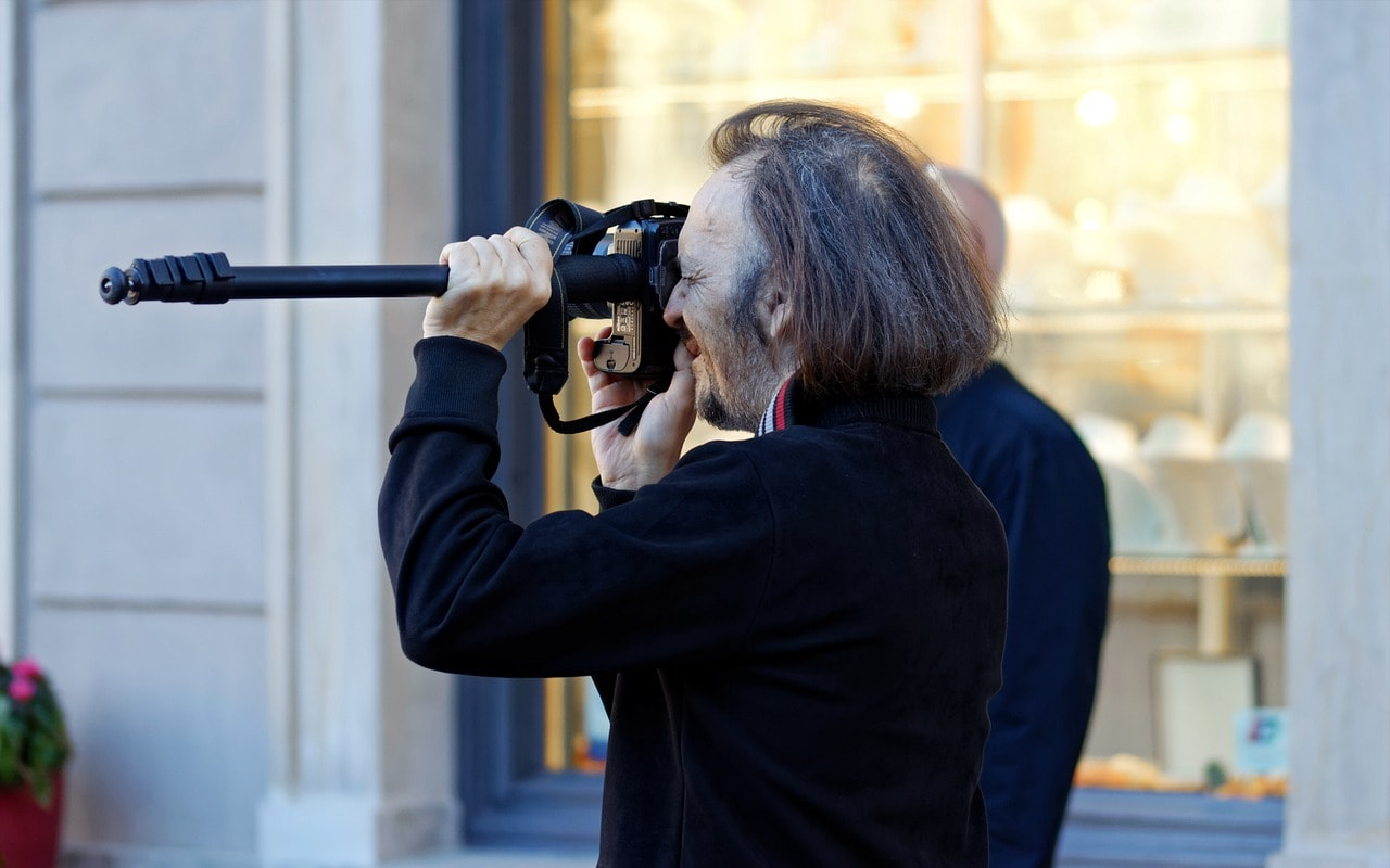 man shooting with camera on monopod