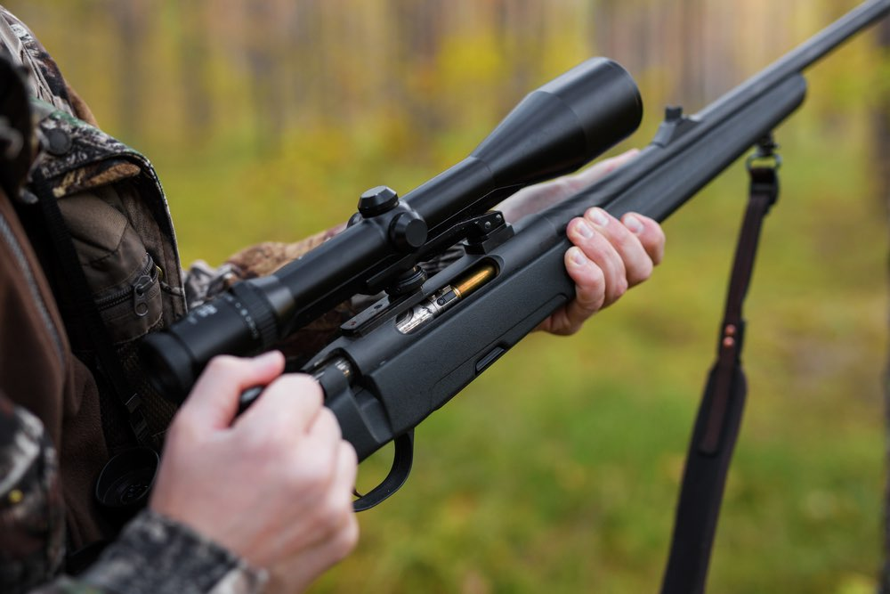 Hunter loading his shotgun with scope